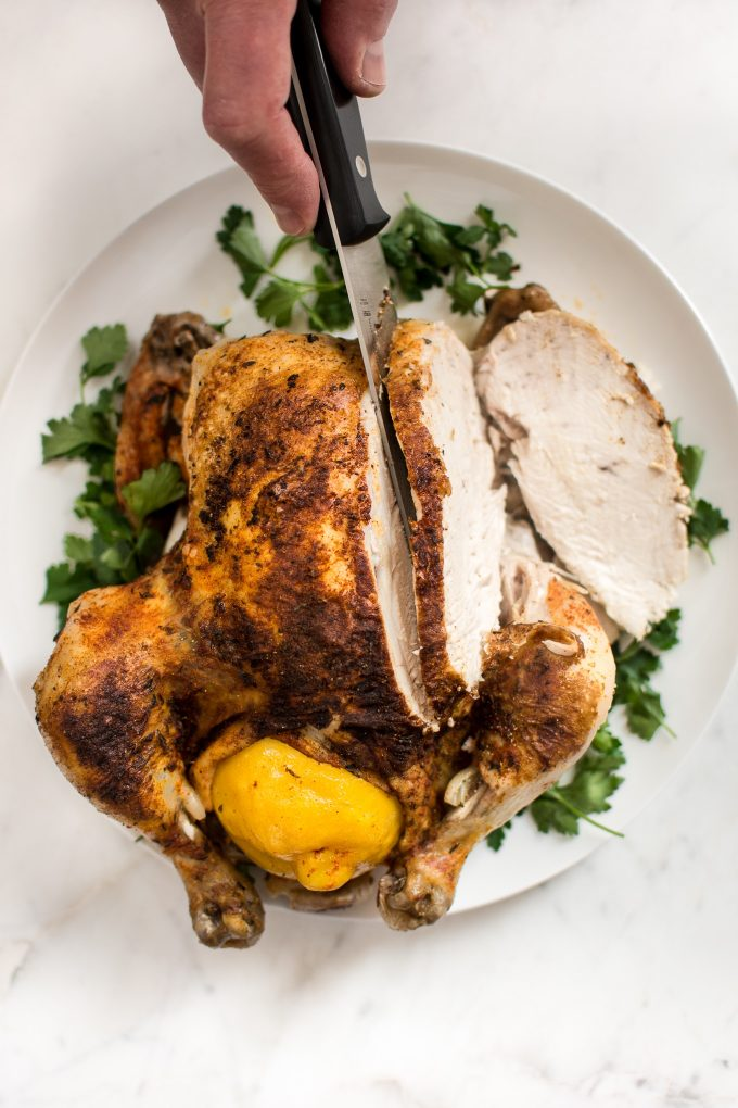 Instant Pot whole chicken on a white serving plate with a knife and parsley garnish