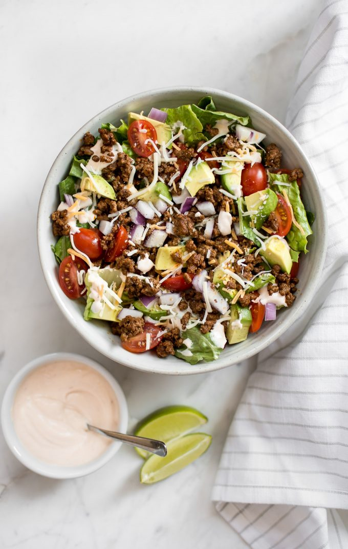 bowl of southwest taco salad beside small dressing bowl with a spoon and lime wedges