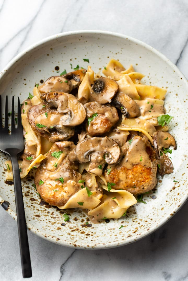 creamy balsamic tenderloin medallions with egg noodles in a shallow bowl