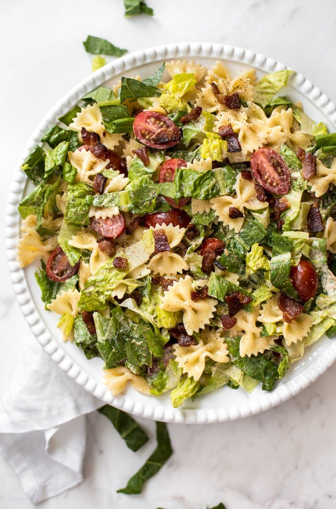 summer pasta salad with bacon, lettuce, tomatoes on a white plate