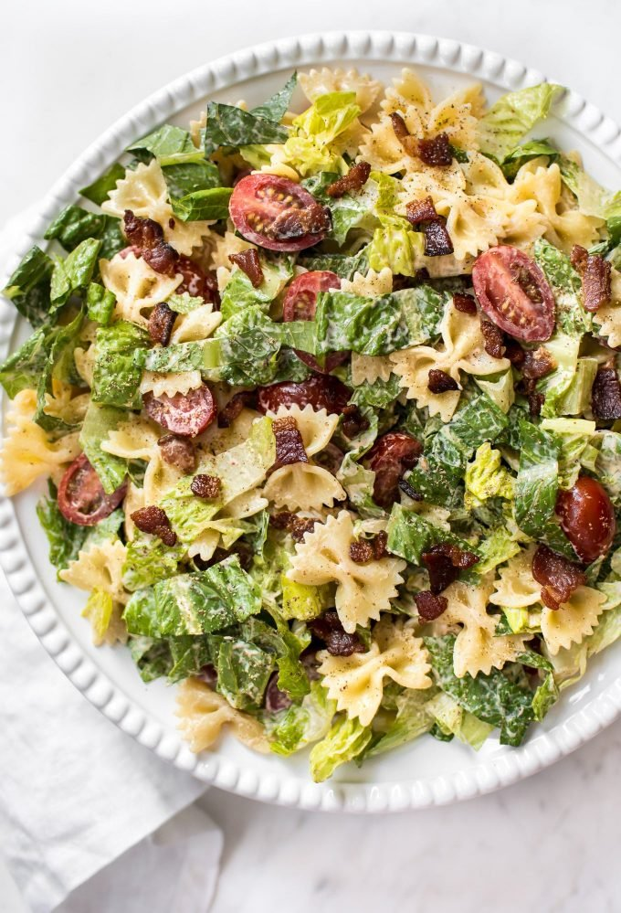 BLT pasta salad with bowtie shaped pasta on a white plate