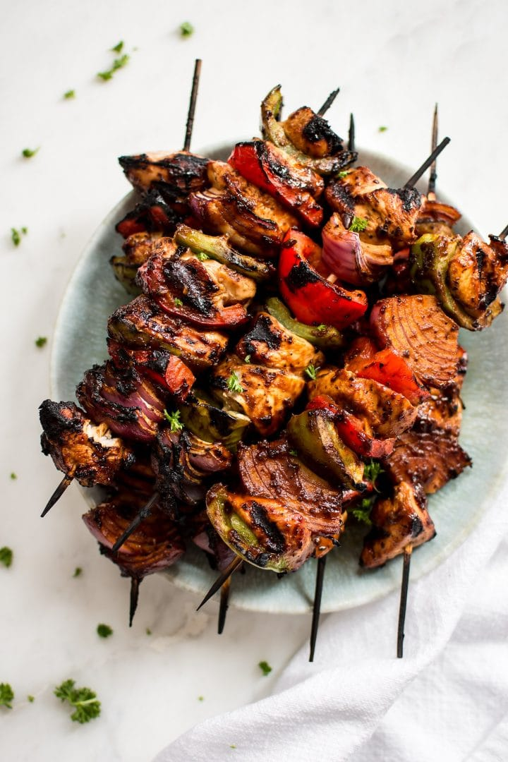 Making chicken kabobs on the grill is fast and easy! A quick marinade, red onions, green and red peppers, and some skewers is all you need to make these healthy chicken kebabs. A delicious summer BBQ recipe!