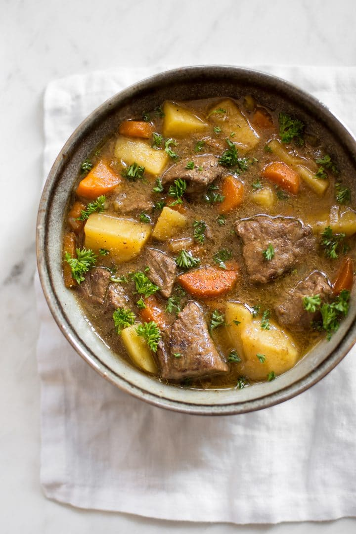 bowl of Irish Instant Pot stew with carrots and potatoes on a marble surface