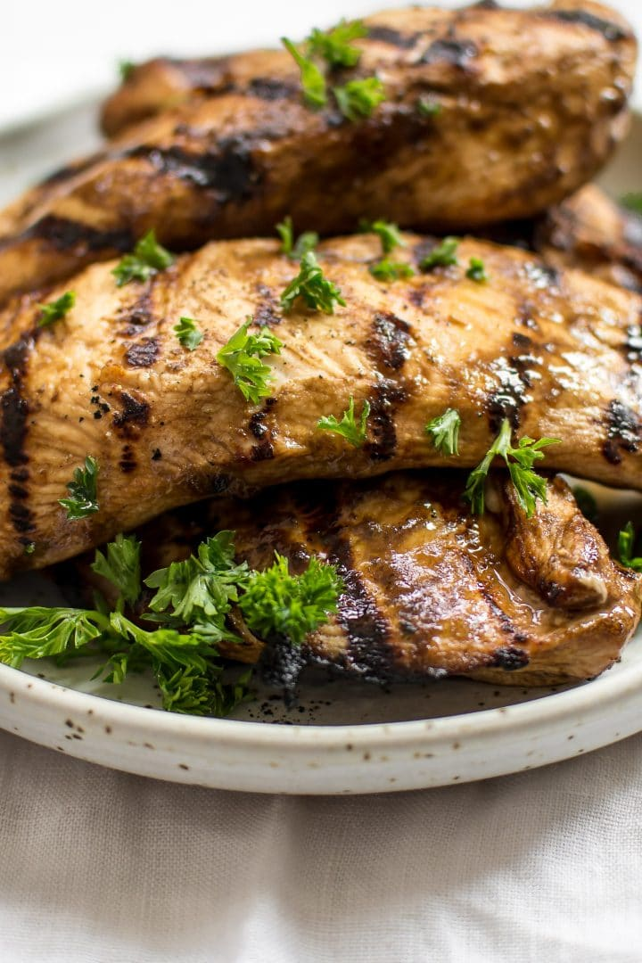 close-up of balsamic grilled chicken on a plate with parsley garnish