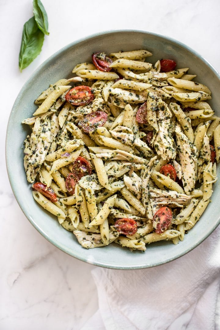 cold pesto pasta salad in a bowl beside basil leaf
