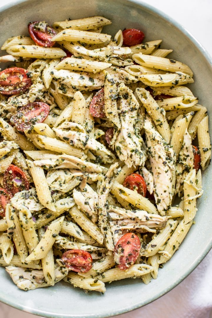 close-up of healthy cold pesto pasta salad with chicken, basil, and fresh tomatoes