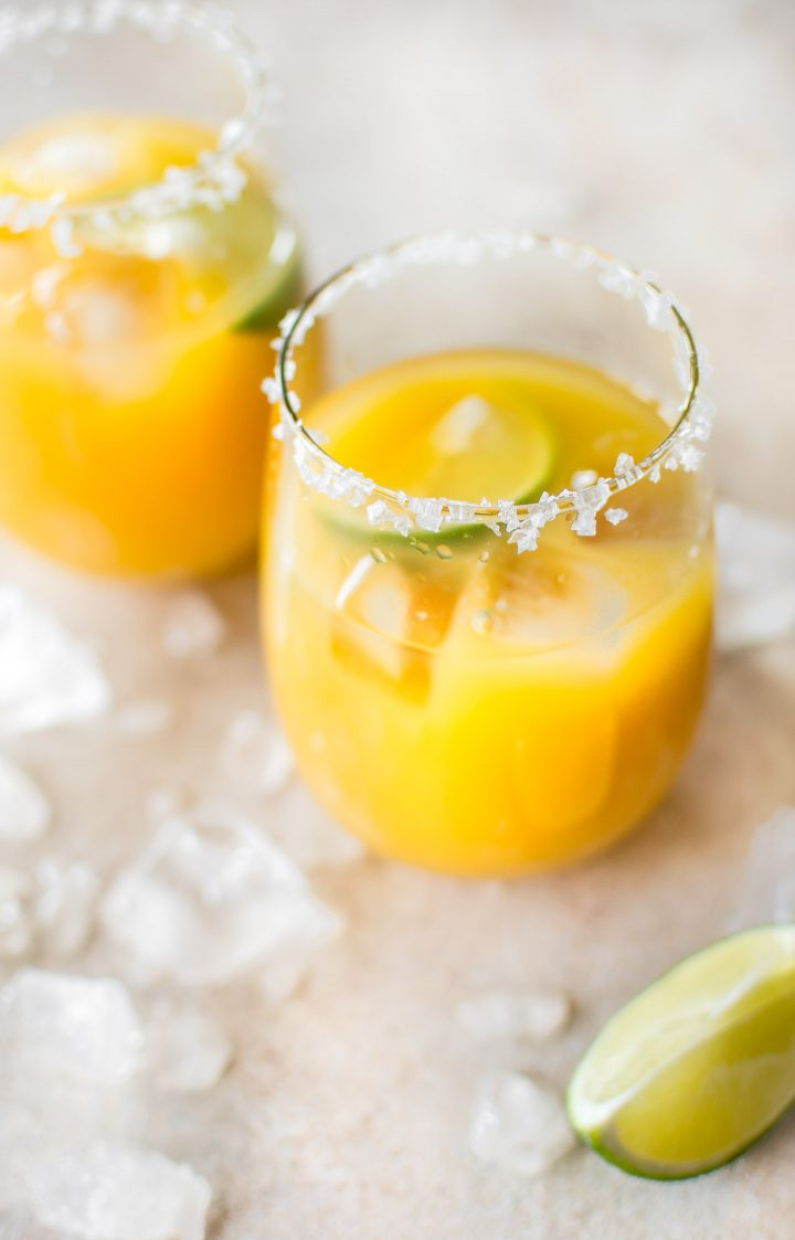 Homemade mango margaritas on the rocks are easy to make and refreshing in the summer! Dust off that tequila and try this simple fruity margarita today.