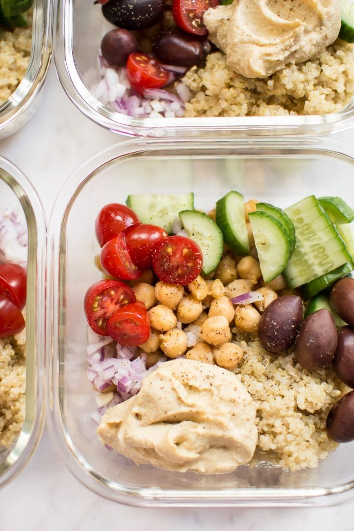 close-up of glass container with cucumber, olives, tomatoes, chickpeas, hummus, and quinoa