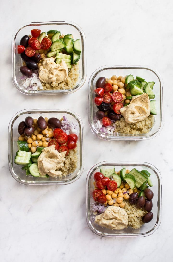 four Mediterranean vegan meal prep bowls with quinoa, chickpeas, hummus, olives, tomatoes, and cucumber