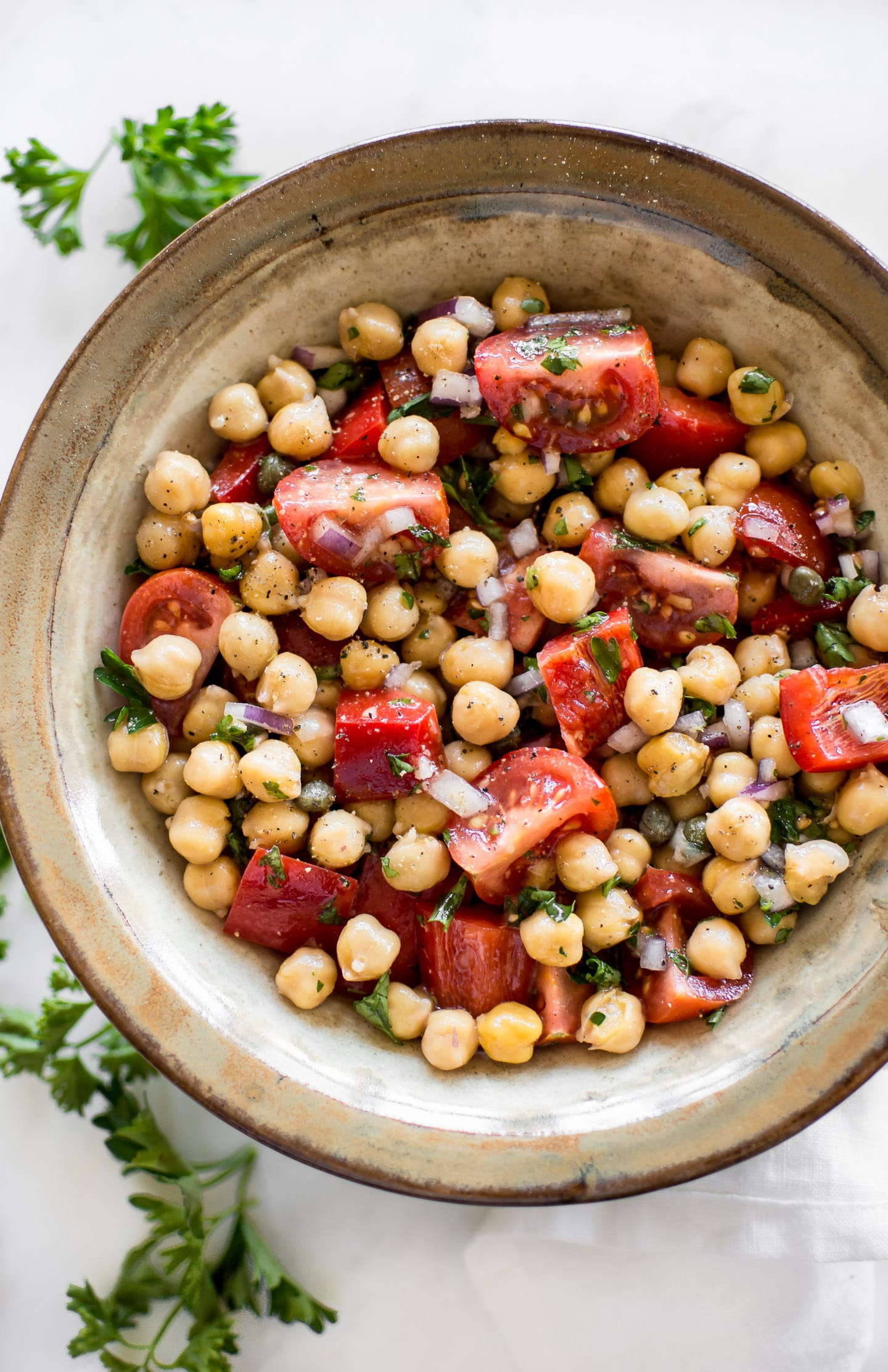 This easy vegan tomato chickpea salad recipe is healthy, delicious, and perfect for summer. You'll love the simple lemon vinaigrette. This cold chickpea salad is great for meal prep.