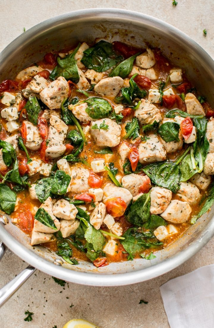 chicken, spinach, tomatoes cooking in a metal skillet
