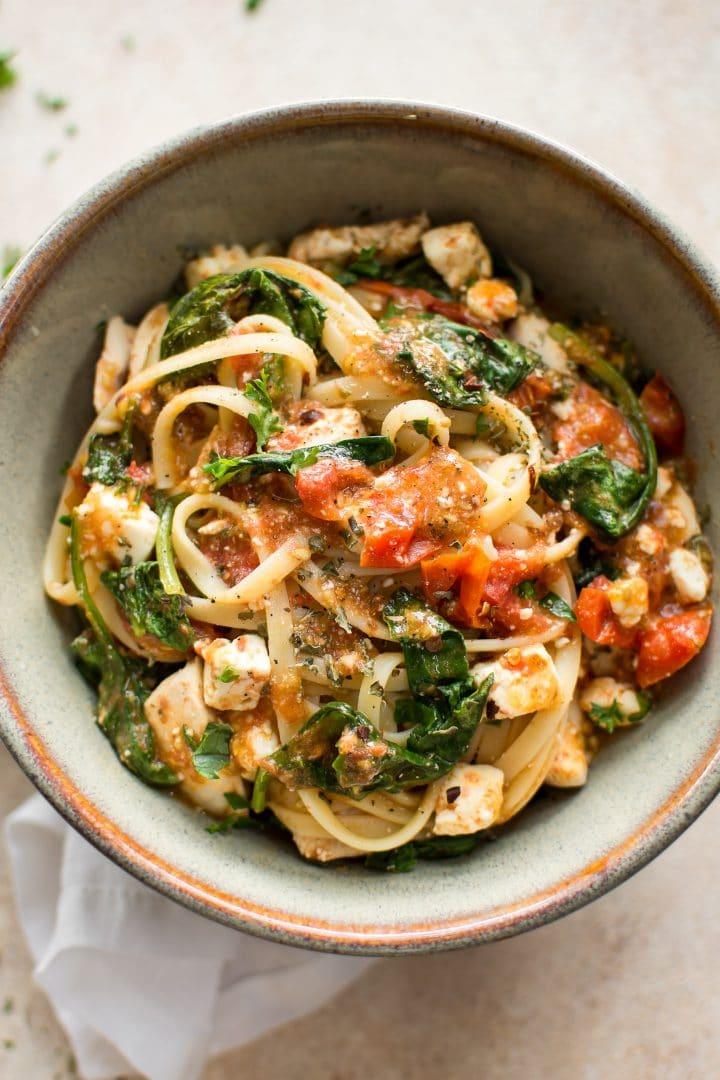 healthy chicken feta spinach pasta in stoneware bowl