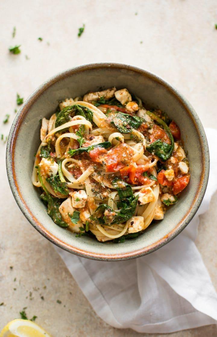 chicken feta spinach pasta in stoneware bowl with a white cloth napkin