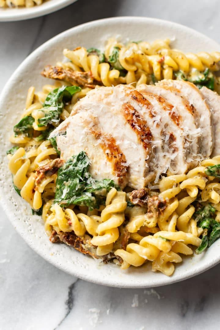chicken pesto pasta in a white bowl