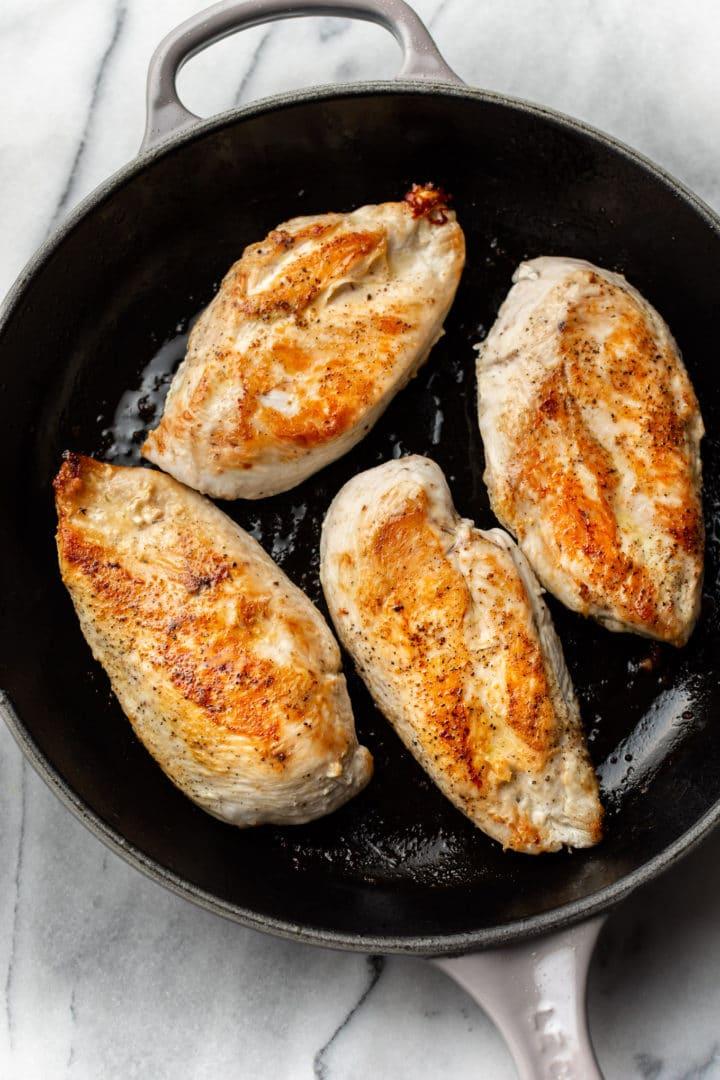 seared chicken in a skillet for chicken pesto pasta