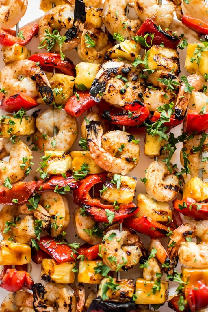 These grilled pineapple shrimp skewers are the perfect easy summer BBQ recipe! The sweet honey glaze, juicy shrimp, and red peppers make the best Hawaiian kabobs.