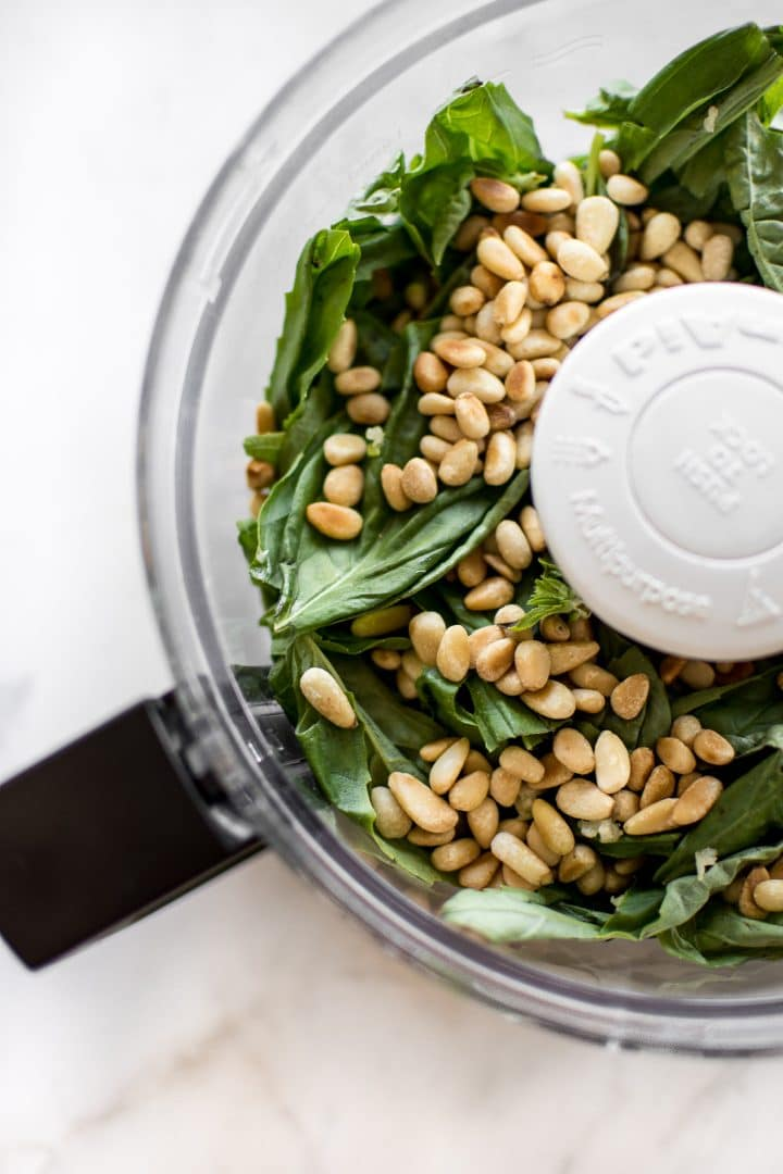 basil and pine nuts in a food processor