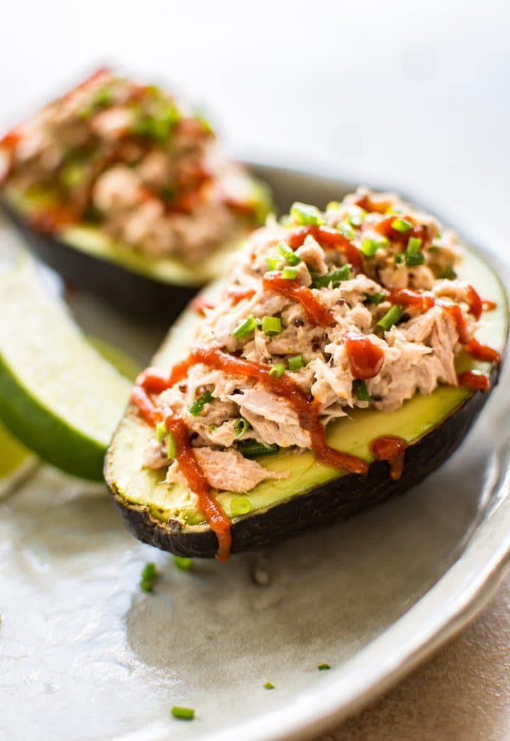 This spicy tuna stuffed avocado is healthy, fast, and delicious. This low-carb keto recipe is ready in only 10 minutes! It's super flavorful with sriracha, lime, mayo, mustard, and chives! An easy lunch idea.