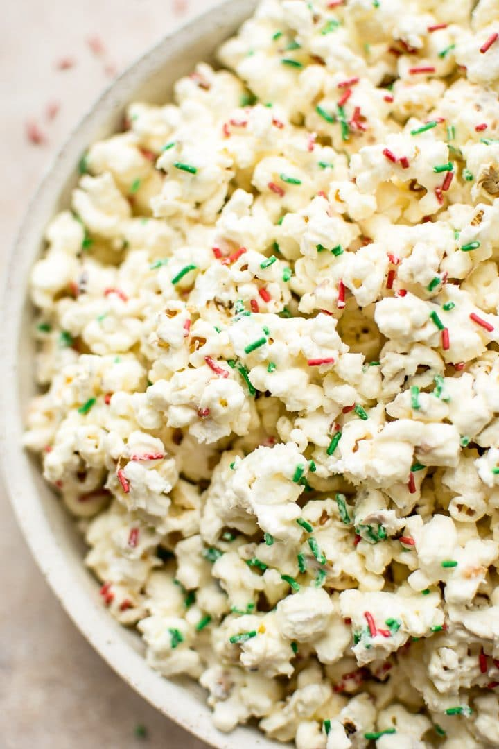 This white chocolate Christmas popcorn recipe is easy and festive. Perfect for Christmas parties! You can easily portion it out into bags for kids' snacks or fun and simple homemade edible Christmas gifts.