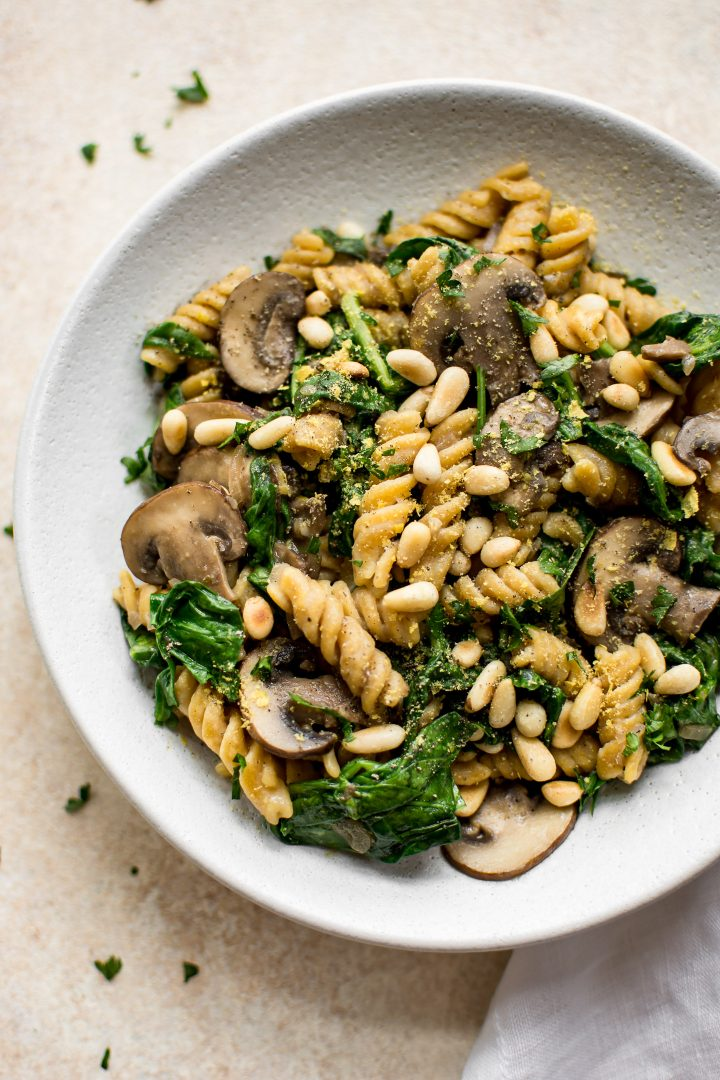 vegan spinach mushroom pasta on a white plate