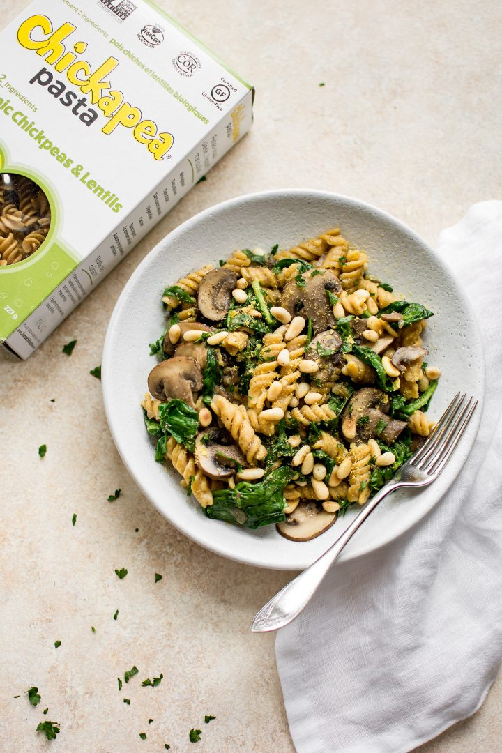vegan mushroom spinach pasta on a white plate with a fork beside a box of Chickapea pasta