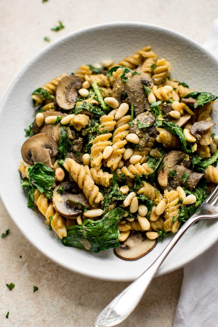 close-up of vegan spinach mushroom pasta on a white plate with a silver fork