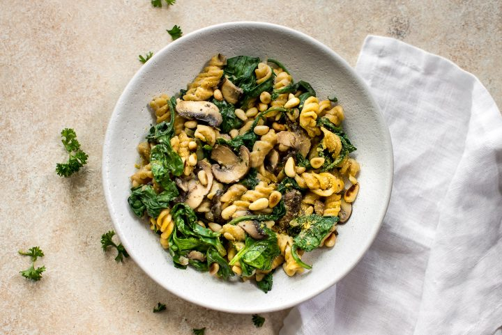vegan spinach and mushroom pasta on a white plate beside a white cloth napkin