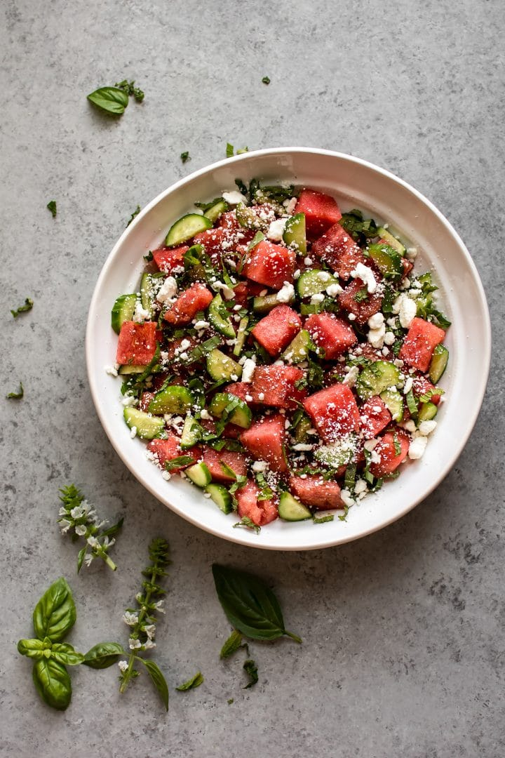 easy watermelon and feta salad in a white bowl on a grey surface with basil leaves