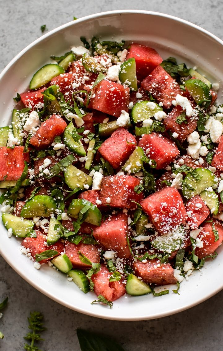 close-up of watermelon, basil, cucumber, and feta salad in a white bowl