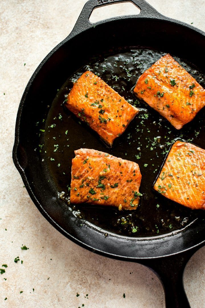 Honey garlic glazed salmon in a cast iron pan. An easy and delicious weeknight recipe!