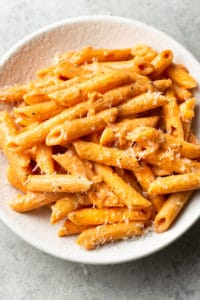 the best penne alla vodka in a white bowl with parmesan cheese grated on top