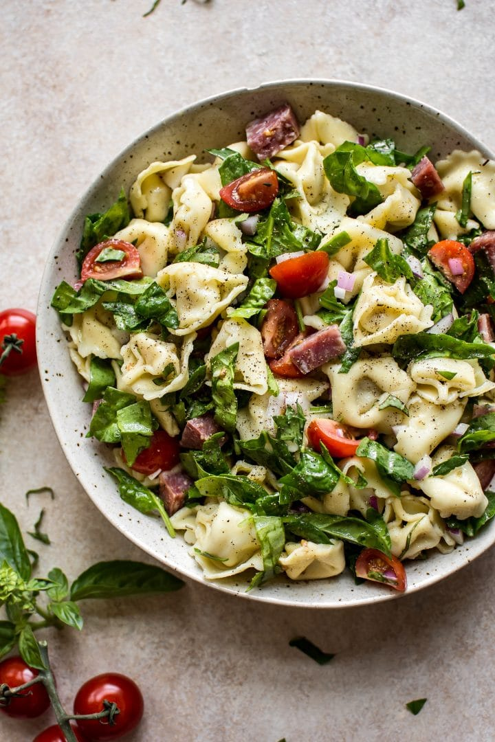This easy cold spinach tortellini salad has a delicious homemade Italian dressing, salami, basil, and fresh tomatoes. The perfect pasta salad to feed a crowd for potlucks, picnics, or summer BBQs.