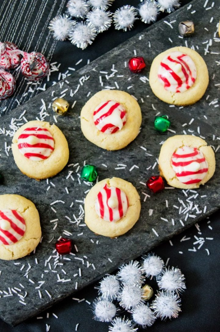 several candy cane Hershey kiss sugar cookies on a dark surface