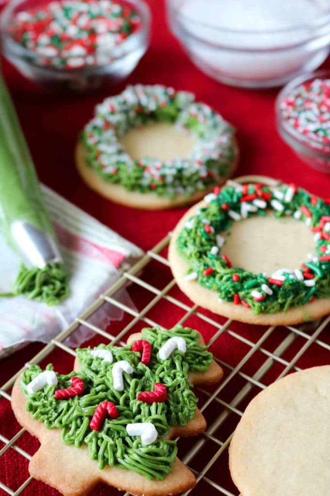 wreath and Christmas tree shaped sugar cookies with buttercream icing on a wire rack