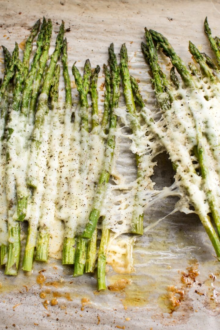 This quick and easy baked cheesy asparagus recipe is keto, low carb, and will soon be your new favorite side dish! Mozzarella, parmesan, and garlic make it extra delicious.