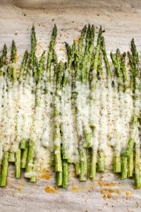 This easy cheesy baked asparagus recipe is the ultimate side dish! It only has a handful of everyday ingredients including parmesan, mozzarella, and garlic. This keto low carb recipe is a definite keeper!