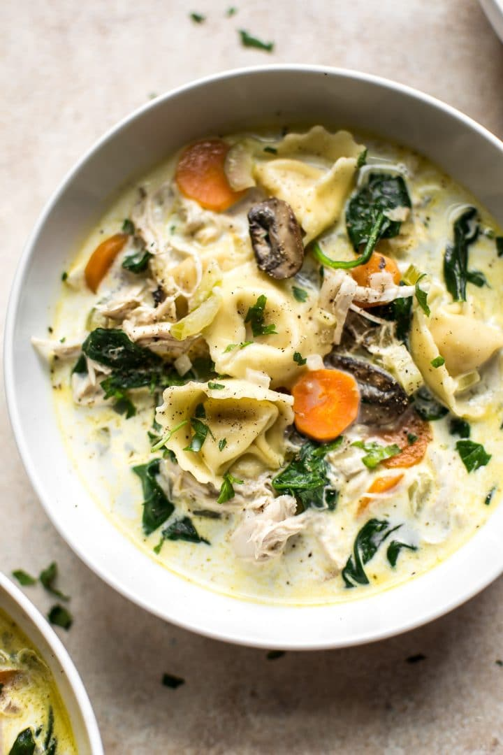 easy creamy spinach tortellini soup with chicken, mushrooms, garlic, and carrots in a white bowl