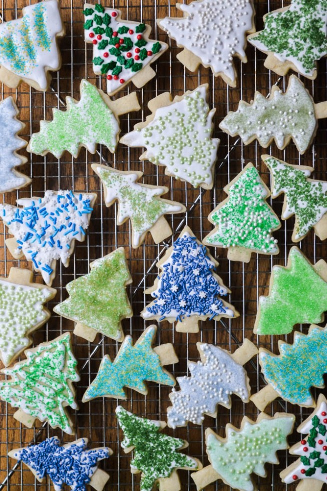 several christmas tree shaped holiday sugar cookies with DIY colored sugar on a wire rack