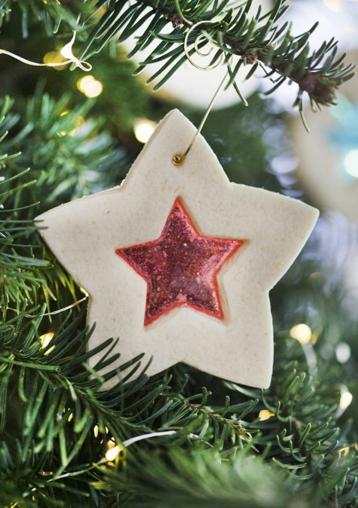 close-up of a star-shaped stained glass sugar cookie on a pine tree