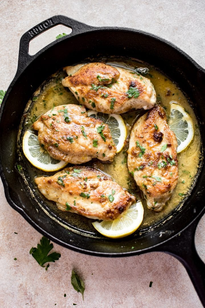 chicken in a cast iron skillet with a lemon butter sauce