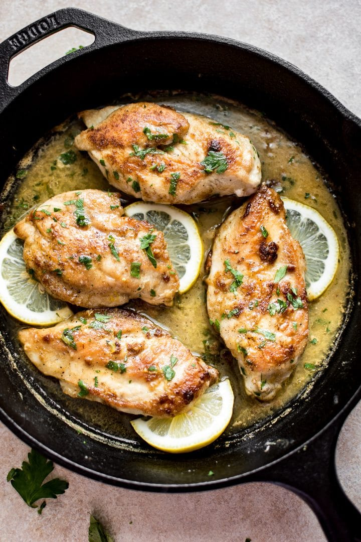 cast iron skillet with lemon butter chicken and lemon slices