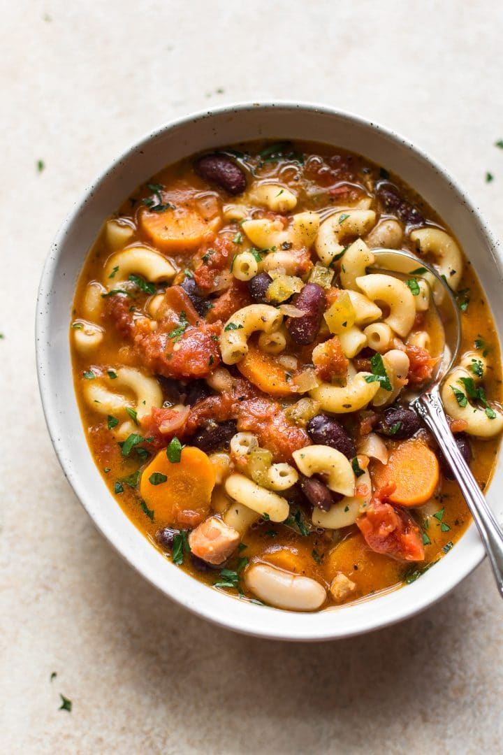 easy pasta e fagioli soup with pancetta in a white bowl with a spoon