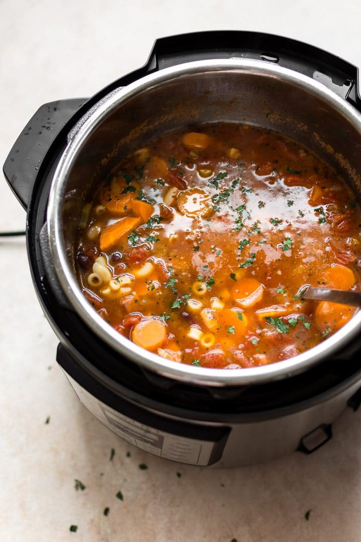 an electric pressure cooker with Instant Pot pasta e fagioli soup and a ladle