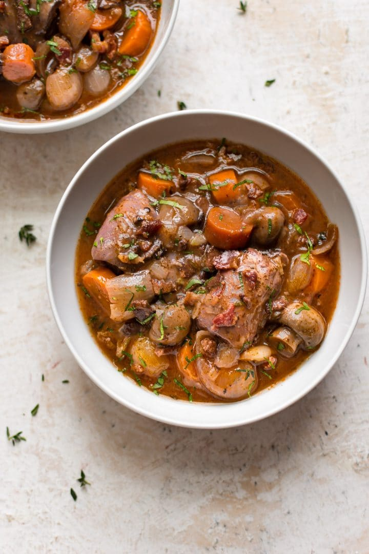 two white bowls with instant pot coq au vin with mushrooms and carrots