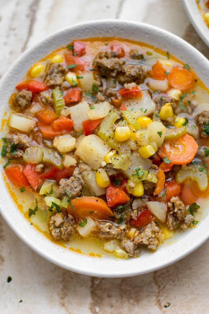 close-up of healthy sausage, corn, and potato soup in a white bowl