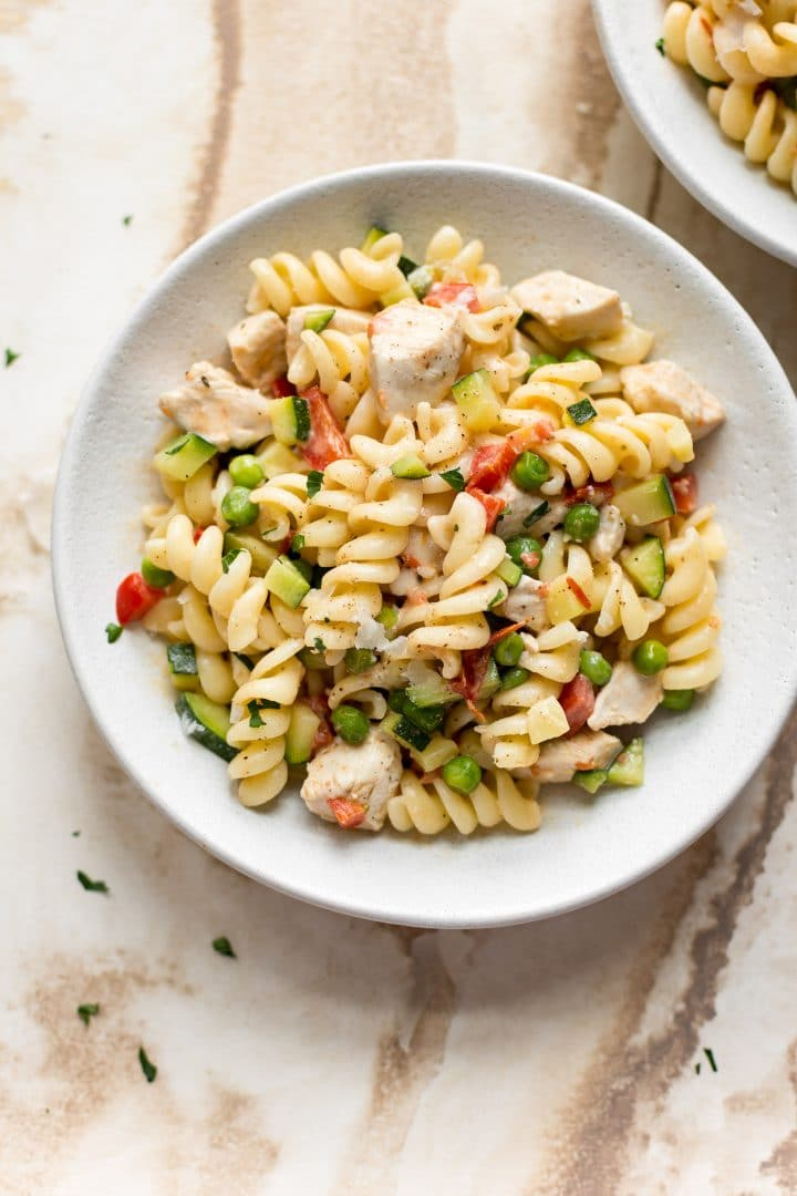 pasta with vegetables and chicken in a white bowl