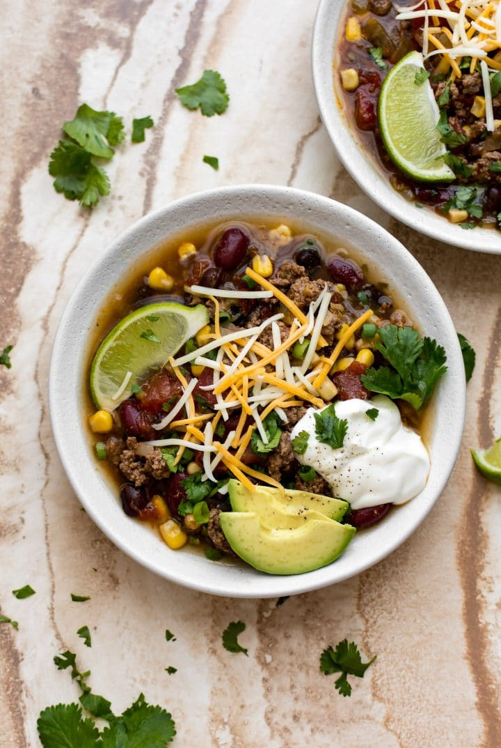 This easy Crockpot taco soup is made with ground beef, corn, beans, and can be topped with anything from sour cream or cheese to avocado and cilantro.