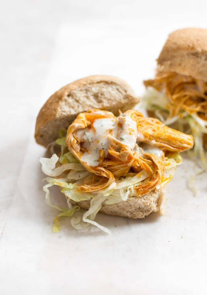 Instant Pot shredded buffalo chicken breast is tender and juicy. Add some ranch, fresh buns, and iceberg lettuce, and you've got the most delicious game day or potluck sandwiches.