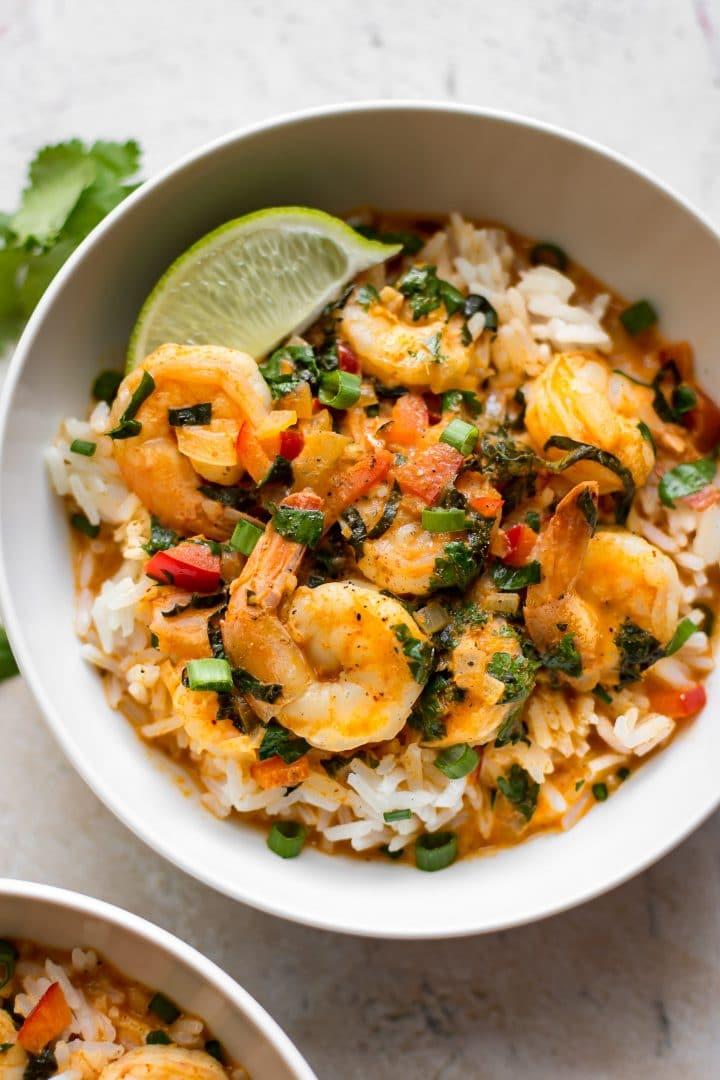 white bowl with close-up of Thai coconut shrimp curry over rice with a lime wedge