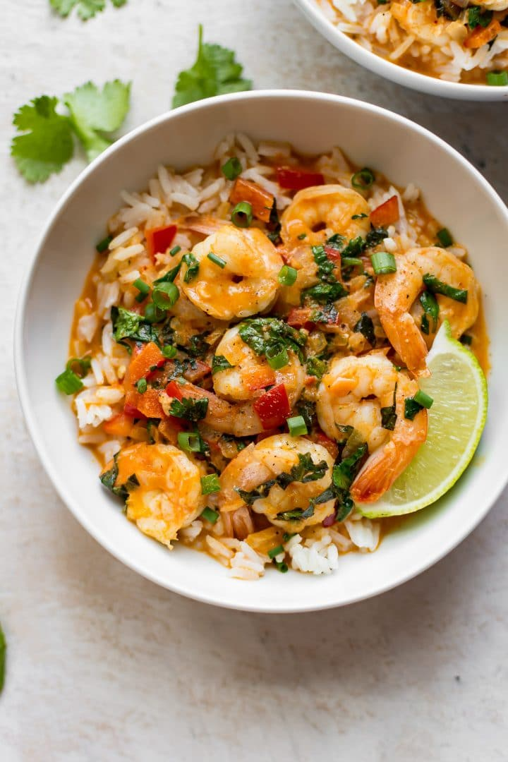 white bowl of Thai red shrimp curry over rice with lime wedge
